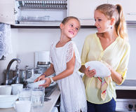 Woman and girl washing dishes Royalty Free Stock Photos