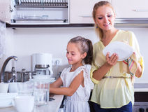 Woman and girl washing dishes Stock Photos