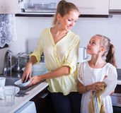 Woman and girl washing dishes Stock Image