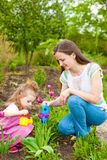 Woman with girl watering flowers Royalty Free Stock Photos