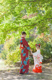 Woman and girl is wearing kimono and walking in the park. Woman and little girl in kimono walking in the city park Stock Photo