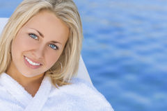 Woman Girl in White Spa Robe Blue Water Background. Beautiful blonde girl young woman in white spa robe with natural blue water background Stock Photo