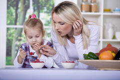Woman and girl with yogurt bowl Stock Image