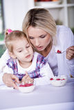 Woman and girl with yogurt bowl Stock Photo