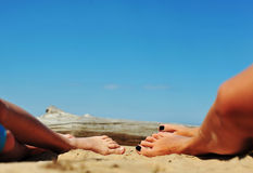 Woman and girls feet in the sand on the beach. Mother and daughter tanned legs and feet stock image