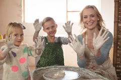 Woman and girls showing hands in pottery shop Royalty Free Stock Photography