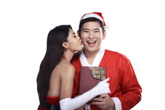 Woman give kiss to man in santa claus costume Royalty Free Stock Photography