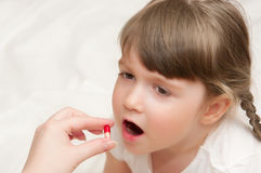 Woman give pill to little girl Royalty Free Stock Photo