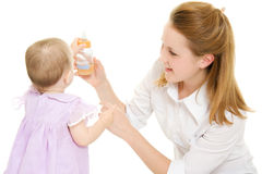 The woman gives the baby a bottle Stock Photo