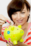 Woman gives coin into ceramic piggy bank Royalty Free Stock Photography