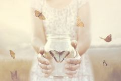 Woman gives freedom to some butterflies enclosed in a glass vase. A young woman gives freedom to some butterflies enclosed in a glass vase stock image