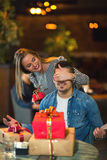 Woman gives a gift to a young man in the cafe Stock Photos