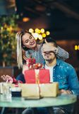 Woman gives a gift to a young man in the cafe Stock Images