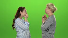 Woman gives the keys to her daughter . Green screen. Side view. Slow motion stock video footage