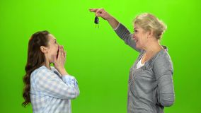 Woman gives the keys to her daughter. Green screen. Side view. Woman gives the keys to her daughter, she embraces and kisses mom. Green screen. Side view stock video