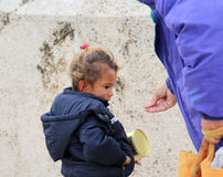 Woman gives money to cute beggar girl downtown of Skopje,capital of Macedonia Royalty Free Stock Photo
