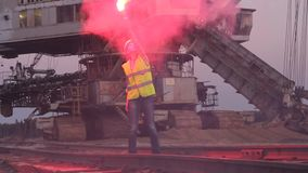 Woman gives a STOP signal for the train with red flare stock footage