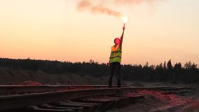 Woman gives a STOP signal for the train with red flare. Outdoors stock footage