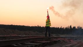 Woman gives a STOP signal for the train with red flare. Outdoors stock video footage