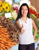 Woman gives thumbs up at Farmers Market. Pretty brunette woman gives thumbs up at Farmers Market surrounded by fresh flowers and vegetables Royalty Free Stock Images