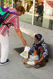 Woman gives to the beggar woman food for her baby Stock Photo