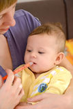 The woman gives to the sick baby medicine by means of the batcher Stock Photography
