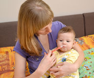 The woman gives to the sick baby medicine by means of the batcher Stock Photo