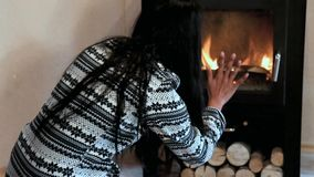 Woman gives wood in the stove stock video footage
