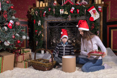 Woman gives wrapped christmas presents gifts to son. Happy women gives wrapped christmas presents gifts to son toddler sitting near Christmas tree royalty free stock photography