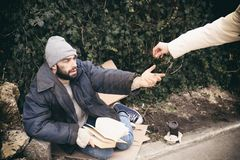 Woman giving alms to poor homeless man on. Street stock images