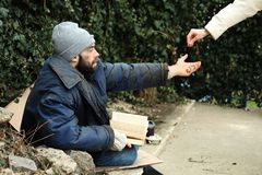 Woman giving alms to poor homeless man. On street stock photo