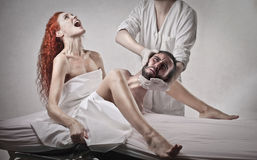 Woman giving birth a grown up man. Woman screaming while giving birth a grown up men helped by a gynecologist Stock Photo