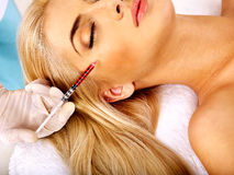Woman giving botox injections. Stock Image