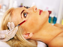 Woman giving botox injections. Stock Photos