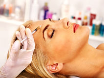 Woman giving botox injections. stock photo