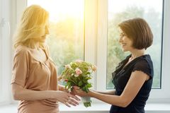 Woman giving bouquet of beautiful flowers to her girlfriend, woman boss. Stock Photos