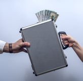 Woman giving briefcase with dollars to man Stock Photography