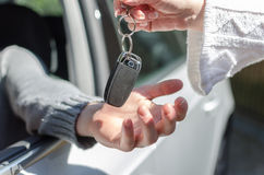 Woman giving car key to a man Stock Image