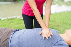 Woman giving cardiopulmonary resuscitation CPR to a man at pub. Woman giving cardiopulmonary resuscitation CPR to a men at public park royalty free stock photos
