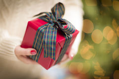 Woman Giving a Christmas Gift Royalty Free Stock Images