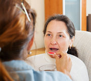 Woman giving the cough syrup to mature mother. At home Stock Images