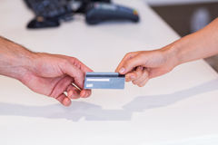 Woman giving credit card to cashier Royalty Free Stock Photos