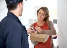 Woman giving a digital signature to post deliverer Royalty Free Stock Photography