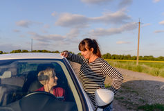 Woman giving directions to a female driver Stock Photo