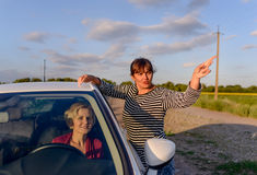 Woman giving directions to a female driver. Who has lost her way on a rural road through fields of sunflowers pointing in the correct direction Royalty Free Stock Images