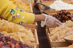 Woman giving dried fruits at the market with plastic gloves Stock Image