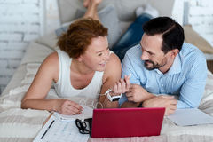 Woman giving earphones to man while lying on bed Stock Photos