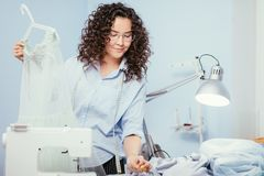 Free Woman Giving Finishing Touch Of Making Dress At Design Studio Stock Photo - 110993620