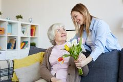 Woman Giving Flowers to Mother royalty free stock photo