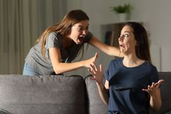 Woman giving a fright to a friend. Sitting on a couch in the living room at home royalty free stock image
